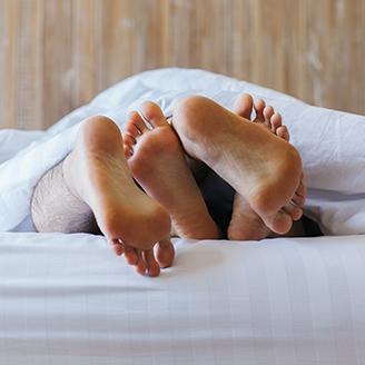 布団からはみ出してる女性の足の裏と覆いかぶさる男の足の裏