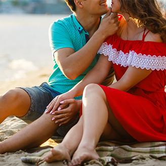 海辺で寄り添って女性の唇を奪おうとする男性