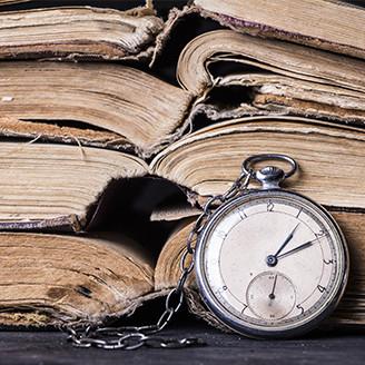 いくつも重なった歴史的書物と時計