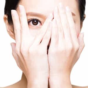 両手で顔を隠して指の間から目だけ出している若い女性