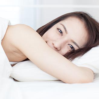 ベッドでうつ伏せになりこちらを見つめる女性