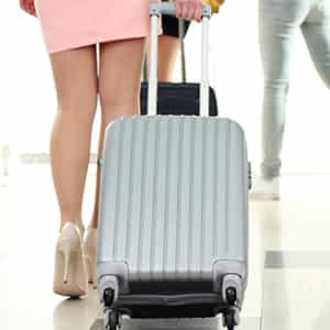 スーツケースを引く女