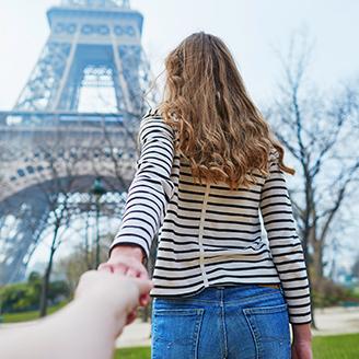パリのエッフェル塔に向かって男性の手を引くボーダーのカットソーを着た女性の後ろ姿