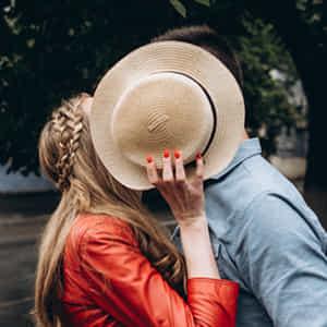 帽子で顔を隠す路上でキスする男女