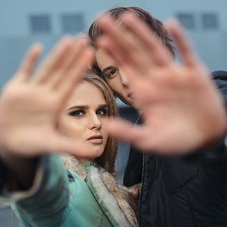 視線を遮るように手をかざすカップル