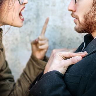 人差し指を立てて激しく問い詰める女性とそれにうろたえる男性