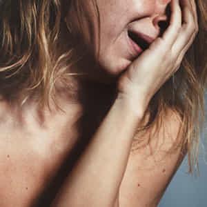 顔に手を当てて涙を流しながら悲しむ女性