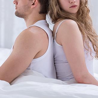 ベッドに背中合わせで腰掛ける男女。女性は男性のことを気にかけるように少し振り返る
