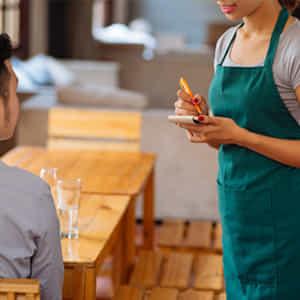 飲食店で働くパートの女性がお客さんからオーダーを聞く